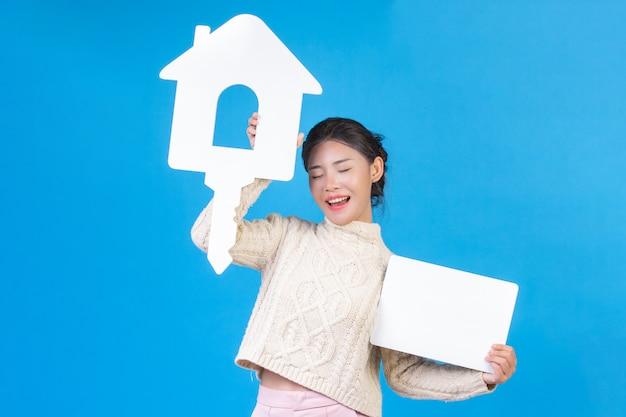Una bella donna che indossa una camicia nuova, un tappeto bianco a maniche lunghe con il simbolo della casa e un cartello bianco su un blu. trading.