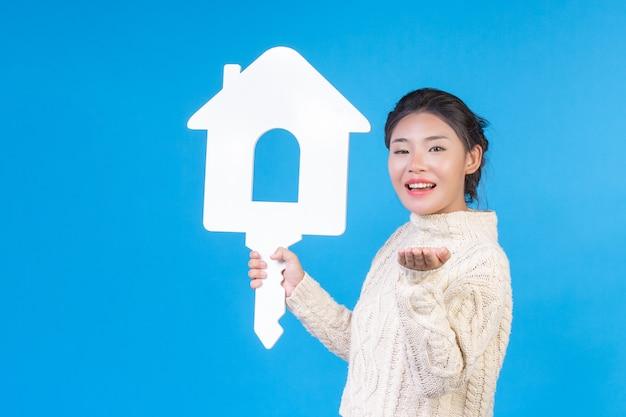 Una bella donna che indossa una nuova camicia bianca a maniche lunghe con un simbolo di casa. commercio di casa.