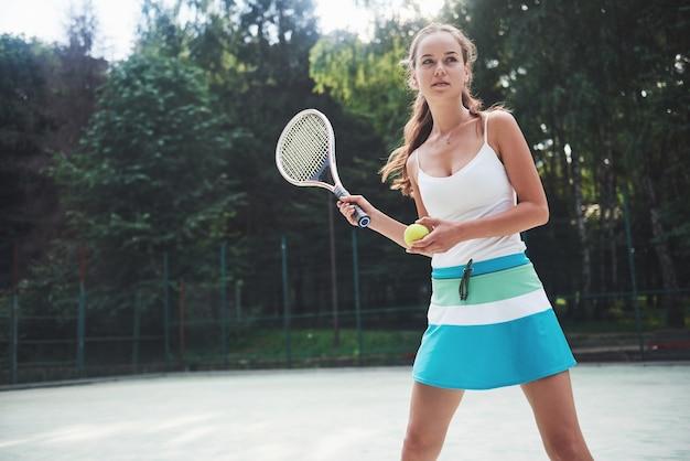 Una bella donna che indossa una palla da tennis degli abiti sportivi.