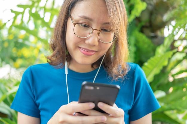 Una bella donna con uno smartphone divertente e sorridente social media digita messaggi di testo,