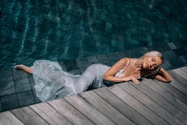 Una bella donna dai capelli biondi con gli occhi chiusi in un lungo abito bianco disteso in piscina.