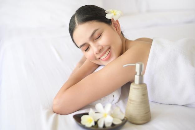 Una bella donna è rilassante e sta massaggiando nella località termale, nel concetto di massaggio e trattamento di bellezza.