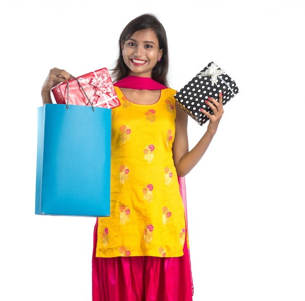 Una bella donna in posa con una borsa della spesa e scatole regalo su uno spazio bianco.