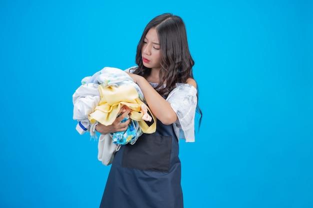 Una bella donna in possesso di un panno preparato per lavare sul blu