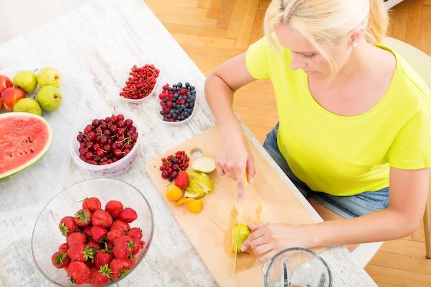 Una bella donna matura che prepara un frullato o un succo di frutta in cucina.