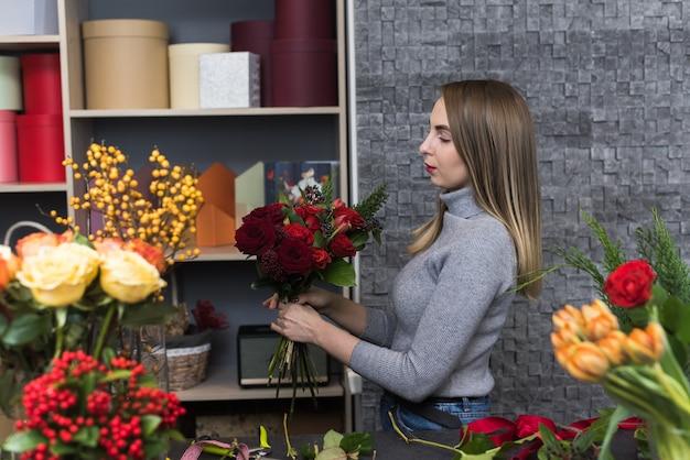 Una bella donna raccoglie un bouquet scuro di rose rosse bordeaux. fiorista maschio che crea bello mazzo nel negozio di fiore. consegna fiori, creazione ordine