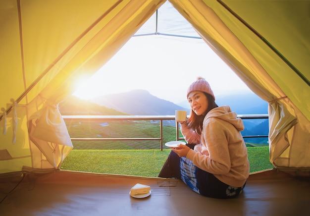 Una bella donna seduta e bere il caffè in una tenda del mattino con una montagna