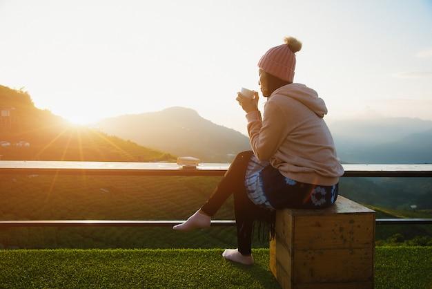 Una bella donna seduta e bere il caffè la mattina con una montagna