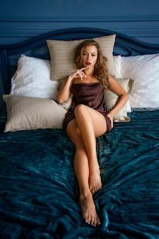 Una bella donna sexy con un trucco luminoso giace in mutande sul letto