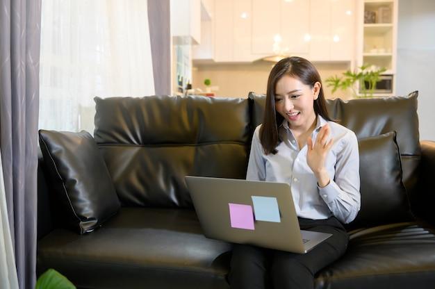 Una bella donna sorridente seduta sul divano sta effettuando una videoconferenza con la famiglia e gli amici in soggiorno