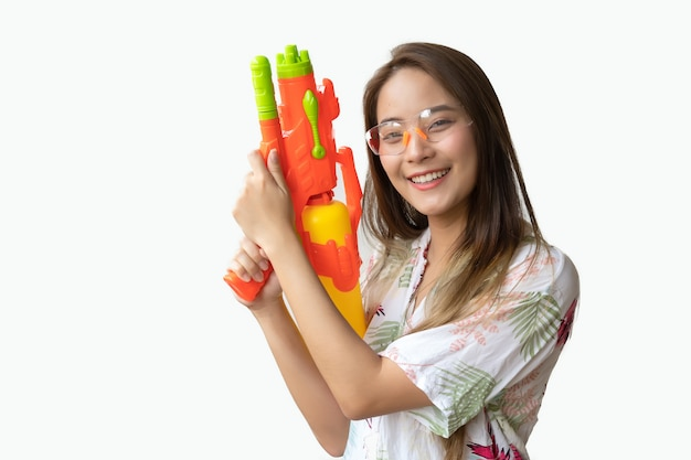 Una bella donna thailandese sorridente fresca e felice, nella sua mano in possesso di una pistola ad acqua nel festival di songkran tailandese su uno sfondo bianco.