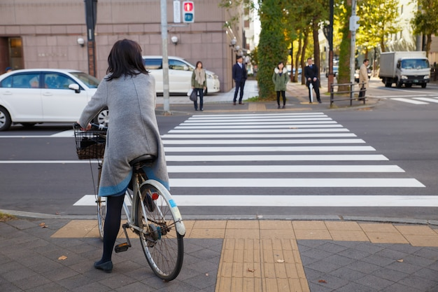 Una bella donna va in bicicletta sul marciapiede e aspetta il semaforo per attraversare la strada.