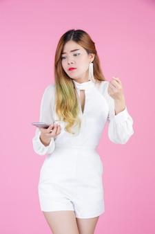 Una bella donna vestita con un abito bianco, mostrando il telefono e le emozioni facciali