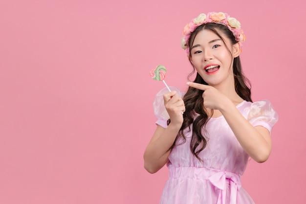 Una bella donna vestita con una principessa rosa sta giocando con le sue dolci caramelle su una rosa.