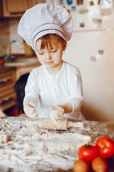 Una bella e giovane figlia sta cucinando in cucina a casa