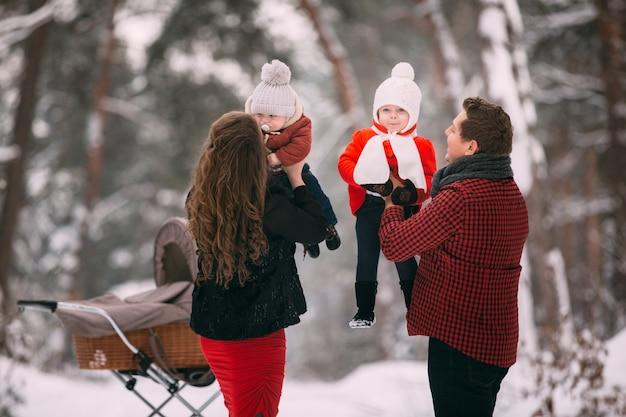 Una bella famiglia che gode nella foresta nevosa di inverno. figlio della madre, del padre, della figlia e del bambino che gode del giorno all'aperto. vacanze, natale, felicità insieme, infanzia innamorata.