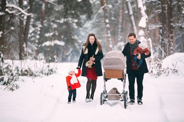 Una bella famiglia con carrozzina retrò cammina attraverso il bosco innevato invernale. figlio della madre, del padre, della figlia e del bambino che gode del giorno all'aperto. vacanze, natale, felicità insieme, infanzia innamorata.