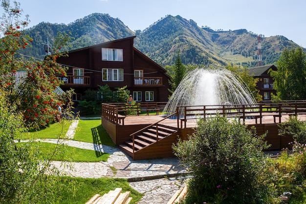 Una bella fontana con acqua di sorgente, ci sono molti alberi verdi, un prato e molte piante