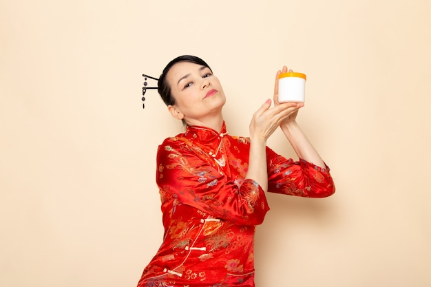 Una bella geisha giapponese di vista frontale in vestito giapponese rosso tradizionale con i bastoncini di capelli che posano la latta della crema della tenuta sulla cerimonia del fondo crema giappone
