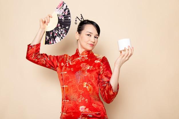 Una bella geisha giapponese di vista frontale in vestito giapponese rosso tradizionale con i bastoncini di capelli che posano tenendo il ventaglio pieghevole e la crema eleganti sulla cerimonia crema giapponese del fondo