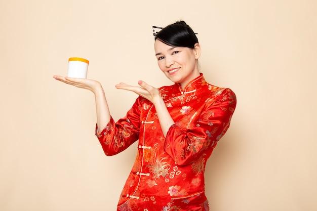 Una bella geisha giapponese di vista frontale in vestito giapponese rosso tradizionale con i bastoncini per capelli che posano la crema della tenuta può sorridere sulla cerimonia crema giapponese del fondo