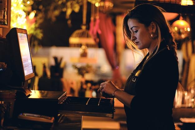 Una bella giovane donna alla scrivania in un ristorante