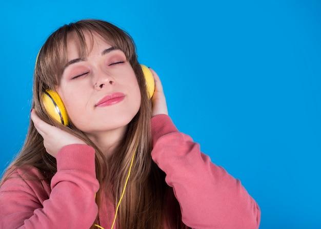 Una bella giovane donna ascolta musica con le cuffie con gli occhi chiusi, sfondo blu
