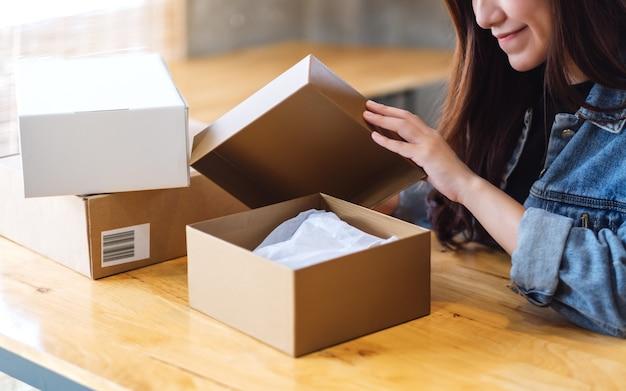 Una bella giovane donna asiatica che riceve e che apre un pacco postale a casa per la consegna e il concetto online di acquisto