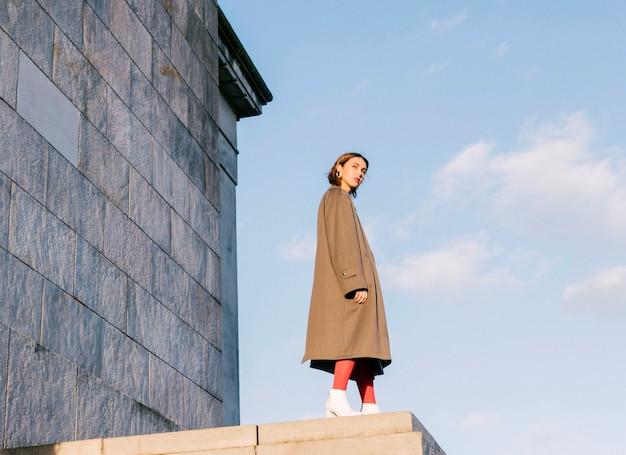 Una bella giovane donna attraente che si leva in piedi davanti alla parete contro il cielo