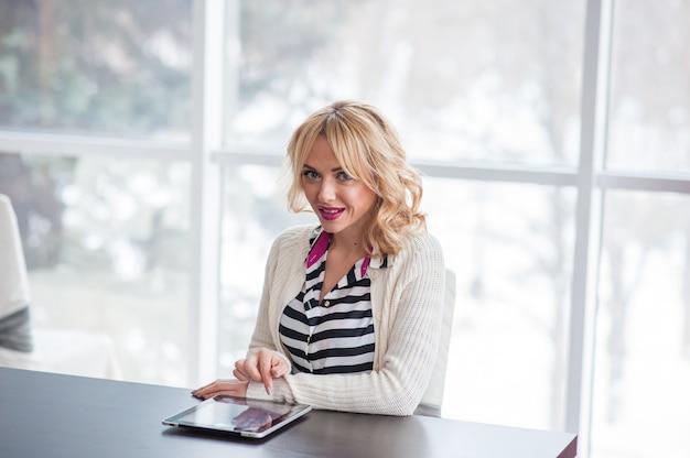 Una bella giovane donna bionda che si siede al tavolo utilizzando un computer portatile.