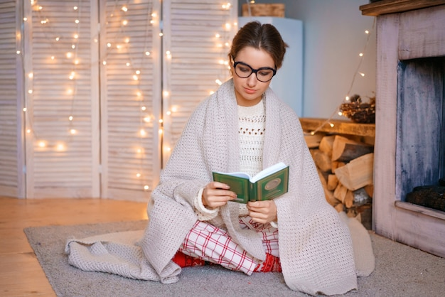Una bella giovane donna con gli occhiali è seduta accanto al caminetto in una coperta e legge un libro