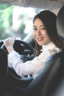 Una bella giovane donna di buon umore viaggia in auto.