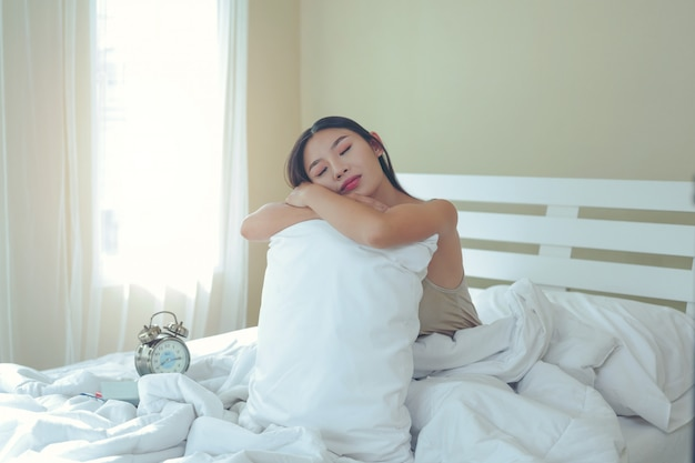 Una bella giovane donna dorme e una sveglia nella camera da letto a casa.