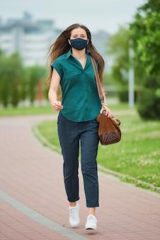 Una bella giovane donna in una maschera medica blu navy salta in possesso di una borsa di pelle nel parco