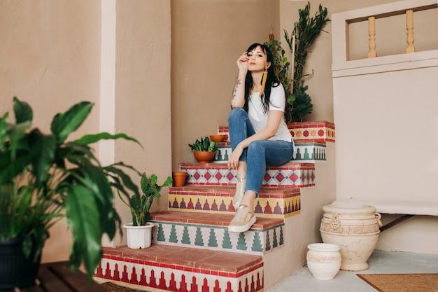 Una bella giovane ragazza asiatica del brunette in jeans e una maglietta bianca è seduta sui gradini con un motivo.