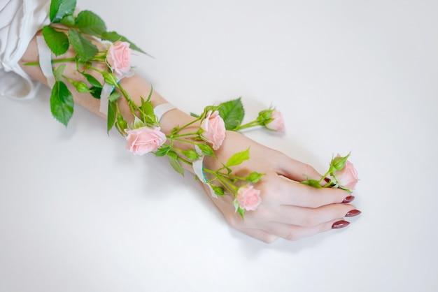 Una bella mano femminile sottile si trova con fiori di rosa su un bianco.