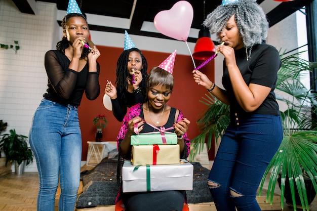 Una bella ragazza africana sorridente apre un regalo alla sua festa di compleanno. le ragazze africane felici in cappelli da festa e con le corna che soffiano sono in piedi intorno alla ragazza e al sorridere di compleanno
