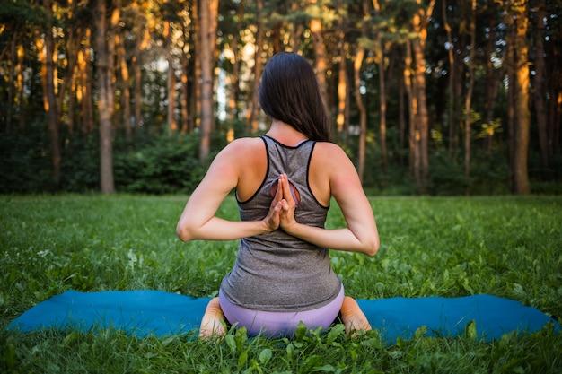 Una bella ragazza atleta si siede indietro ed esegue esercizi di yoga in natura