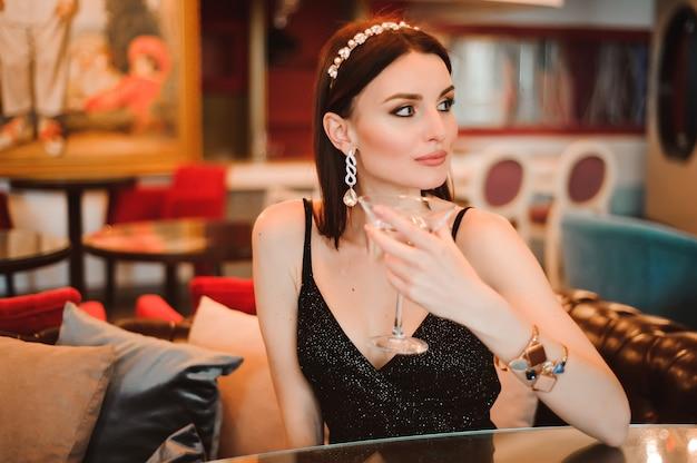 Una bella ragazza beve martini nella hall dell'hotel