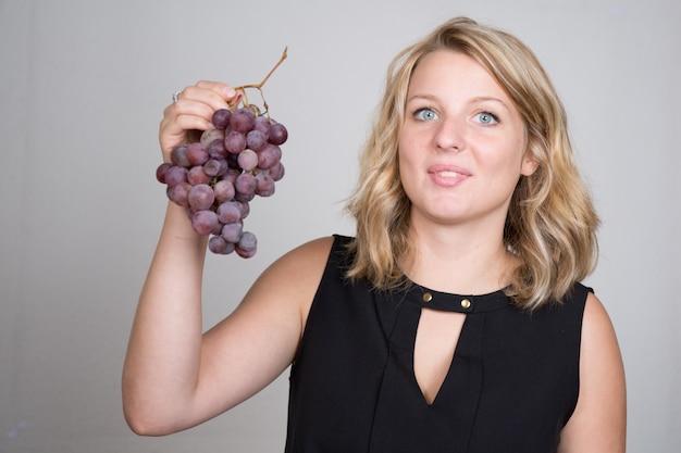 Una bella ragazza bionda che mangia un grappolo di uva nera