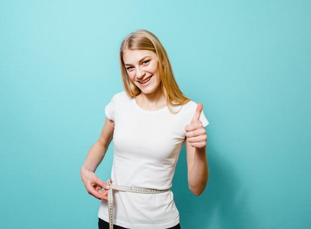Una bella ragazza bionda che misura la sua vita ed è delusa da lei su uno sfondo blu