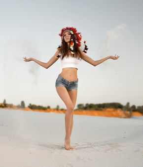 Una bella ragazza caucasica in top bianco e shorts in denim. sulla sua testa indossa un cappello indiano triotto. in piedi nel deserto.