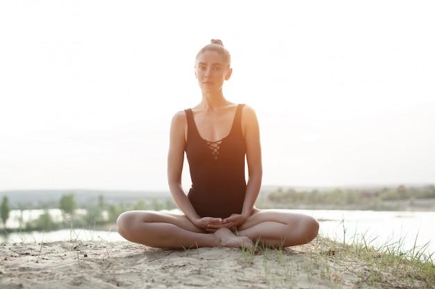 Una bella ragazza caucasica in un costume da bagno nero è seduta nella posizione del loto sulla natura