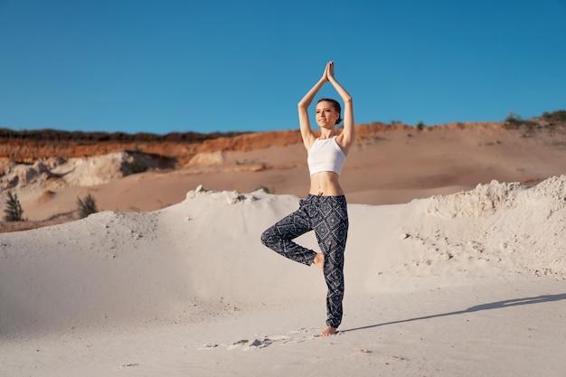 Una bella ragazza caucasica in un top bianco e pantaloni larghi in piedi in una posizione ad albero sulla spiaggia sulla sabbia. con spazio di copia