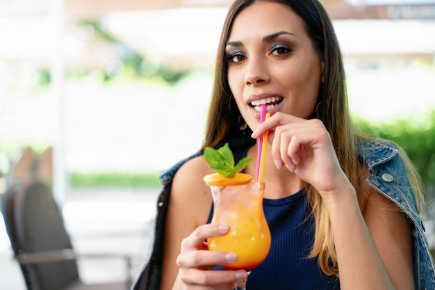 Una bella ragazza che beve un cocktail estivo esotica