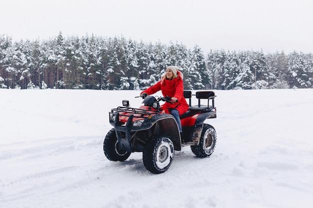 Una bella ragazza che cavalca un quadrociclo in una pittoresca zona nevosa