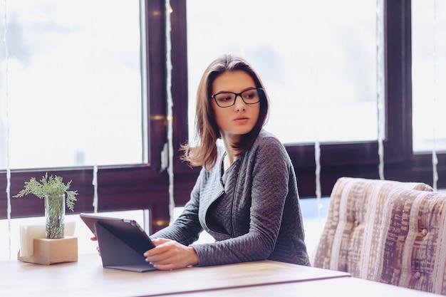 Una bella ragazza con gli occhiali lavora su un tavolino da caffè