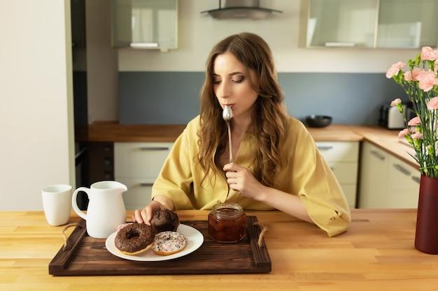 Una bella ragazza con i capelli lunghi è seduta a casa in cucina e sta pianificando di fare colazione.