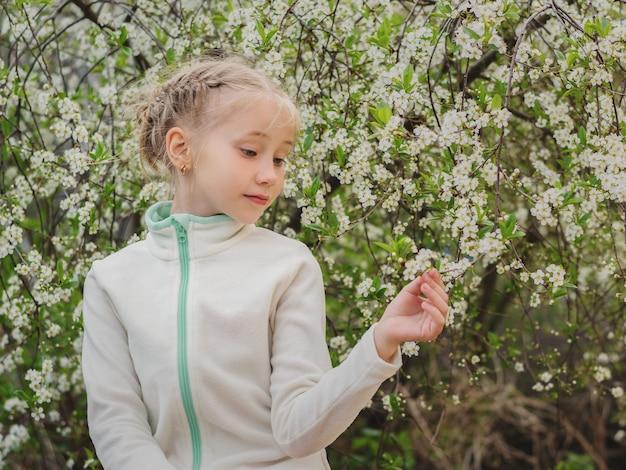 Una bella ragazza con interesse guarda il fiore di ciliegio nel giardino primaverile.