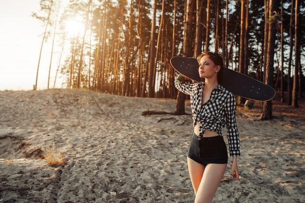 Una bella ragazza con un longboard nelle sue mani in natura in una foresta di pini